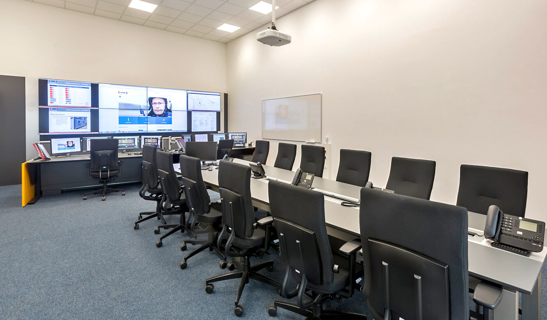 JST - Autorisierte Stelle Digitalfunk Niedersachsen: Lageraum mit Konferenztisch und Großbildwand