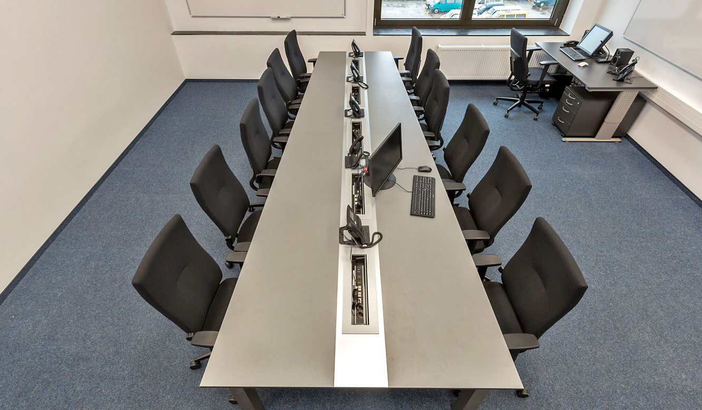 JST - Autorisierte Stelle Digitalfunk Niedersachsen: AllMedia-Konferenztisch in Trapezform für optimierten Blick auf die Großbildwand