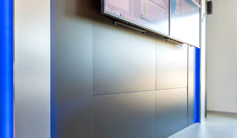 JST-Niedersächsische Wach- und Schließgesellschaft: flächenbündige Revisionbsklappen verbergen sich in der Displaywall