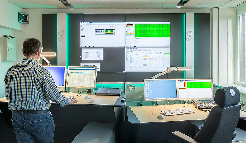JST Dataport Leitstellentische vor der Großbildwand in Stehhöhe