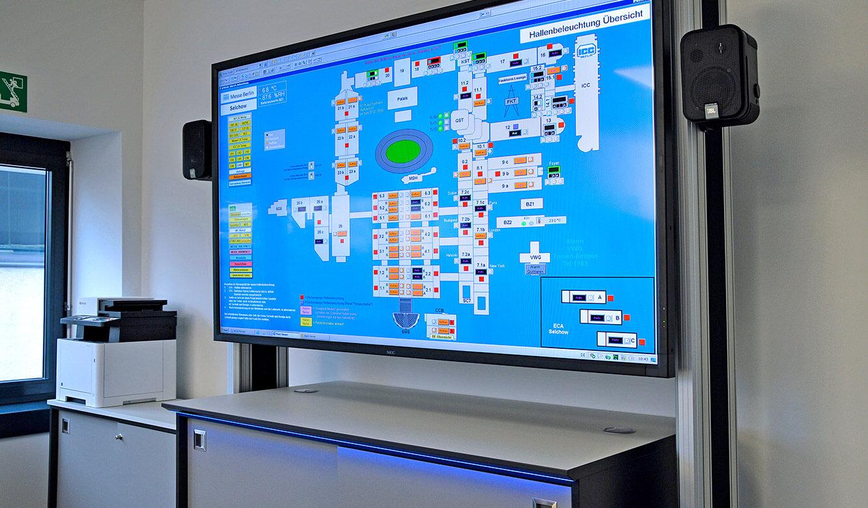 JST-Messe Berlin: 80-Zoll großes LC-Display mit passendem Rack und Medienboard im Krisenraum