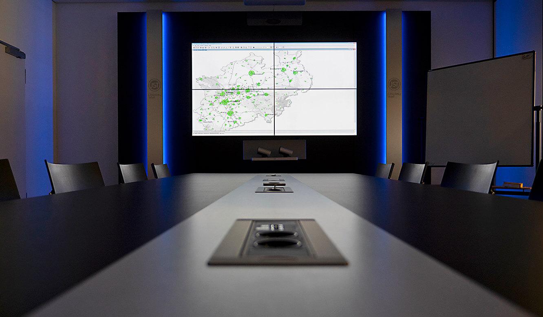JST-IT.NRW: Allmedia-Konferenztisch und Großbildleinwand im Besprechungsraum